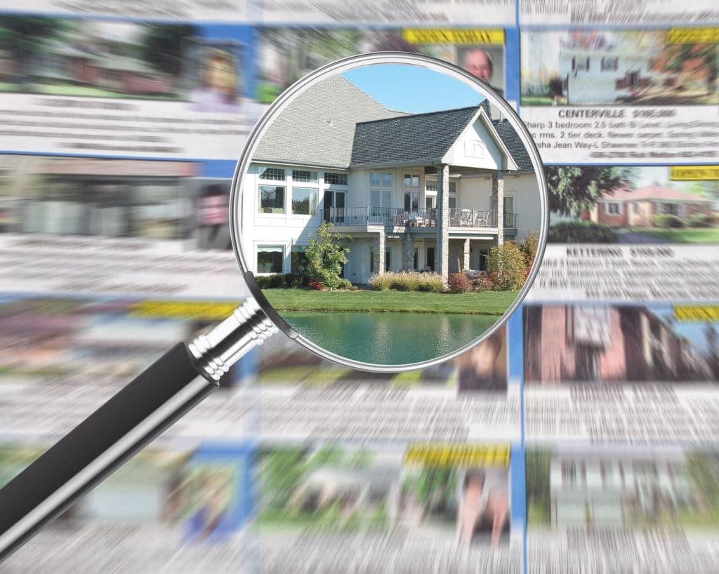 magnifying glass overlooking homes in a newspaper