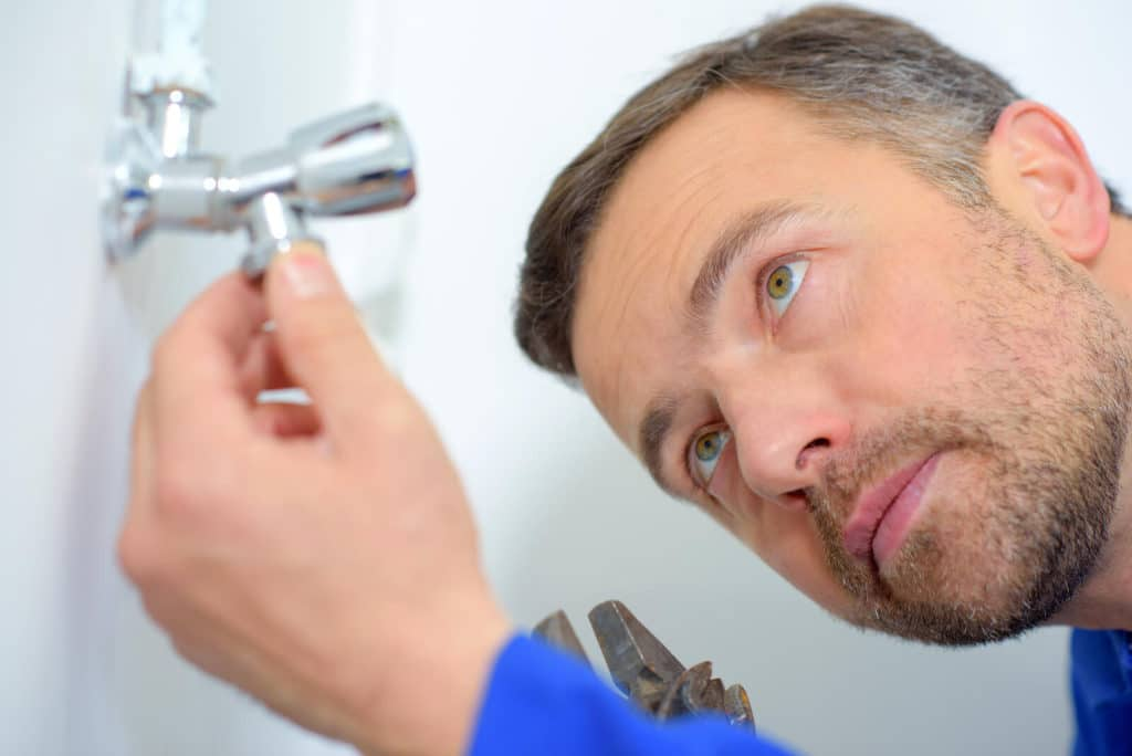 home inspector looking at a faucet