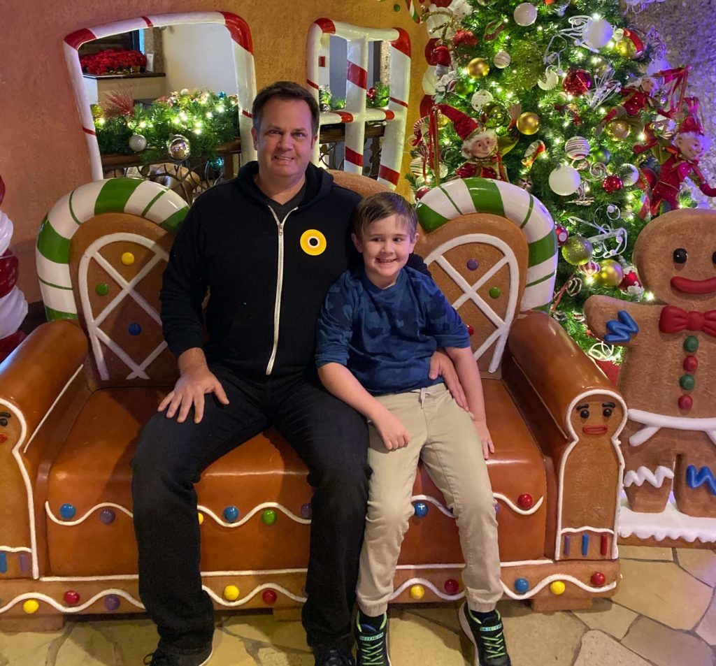 jeff kropp and his sun sitting in front of a ginger bread house